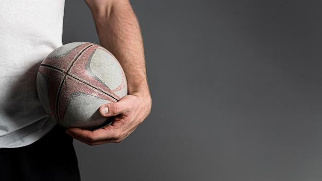 Vorderansicht des männlichen rugbyspielers, der ball neben hüfte mit kopienraum hält