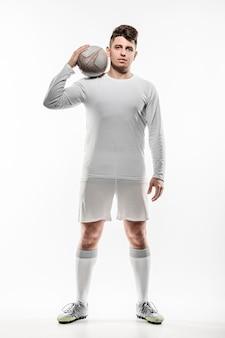 Vorderansicht des männlichen rugbyspielers, der mit ball aufwirft