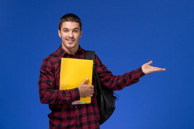 Vorderansicht des männlichen schülers im roten karierten hemd mit dem rucksack, der gelbe dateien an der blauen wand hält