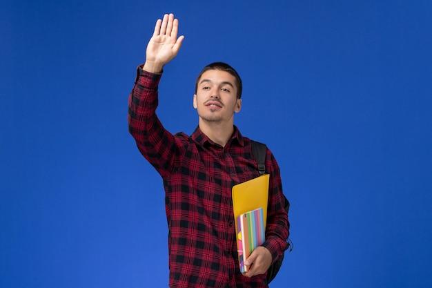 Vorderansicht des männlichen schülers im roten karierten hemd mit rucksack, der dateien und hefte hält, die seine hand auf blauer wand winken