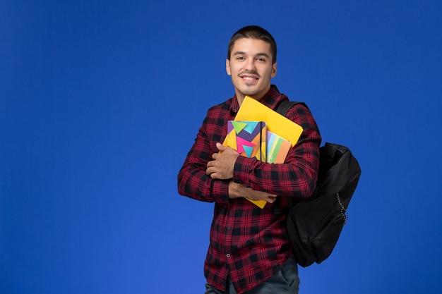 Vorderansicht des männlichen schülers im roten karierten hemd mit rucksack, der heft und akten an der hellblauen wand hält