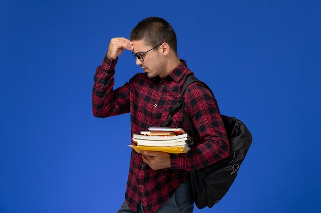 Vorderansicht des männlichen schülers im roten karierten hemd mit rucksack, der hefte und hefte auf hellblauer wand hält