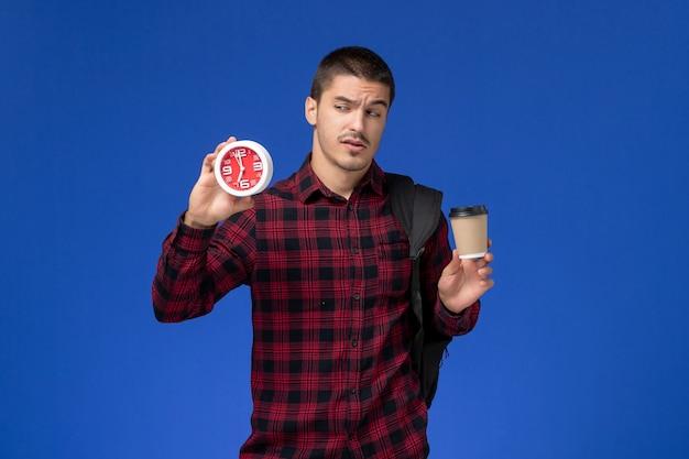 Vorderansicht des männlichen schülers im roten karierten hemd mit rucksack, der uhren und kaffee an der blauen wand hält