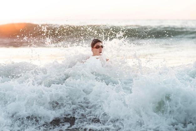 Vorderansicht des männlichen schwimmers, der im ozean schwimmt