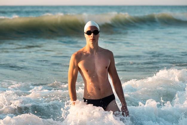Vorderansicht des männlichen schwimmers, der während im ozean aufwirft