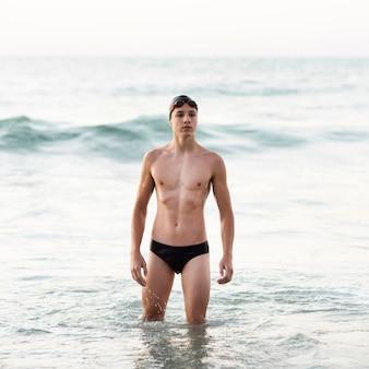 Vorderansicht des männlichen schwimmers mit schutzbrille, die im ozean aufwirft