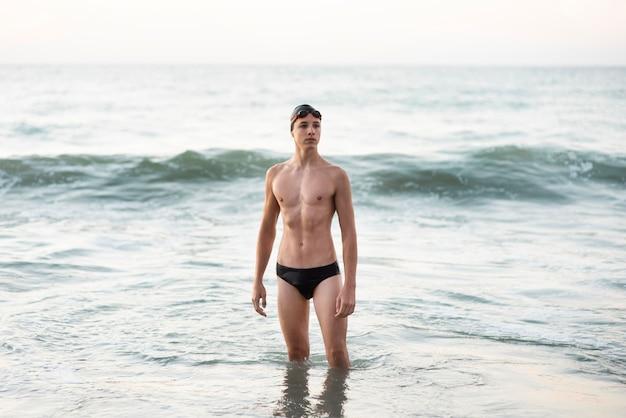 Vorderansicht des männlichen schwimmers mit schutzbrille und mütze, die im ozean aufwirft