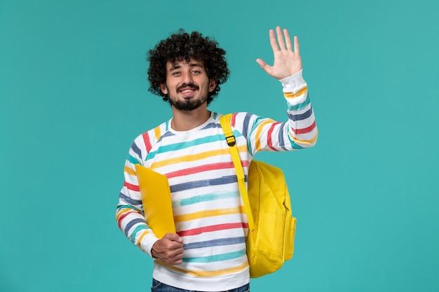 Vorderansicht des männlichen studenten, der gelben rucksack hält, der dateien auf blauer wand hält