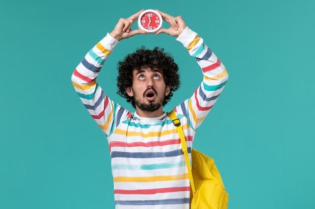 Vorderansicht des männlichen studenten, der gelben rucksack hält, der uhren auf blauer wand hält