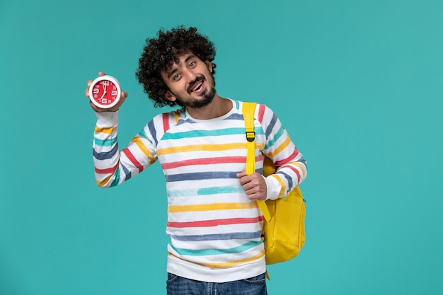 Vorderansicht des männlichen studenten, der gelben rucksack hält, der uhren auf hellblauer wand hält