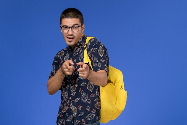 Vorderansicht des männlichen studenten im dunklen hemd, das gelben rucksack auf der hellblauen wand trägt