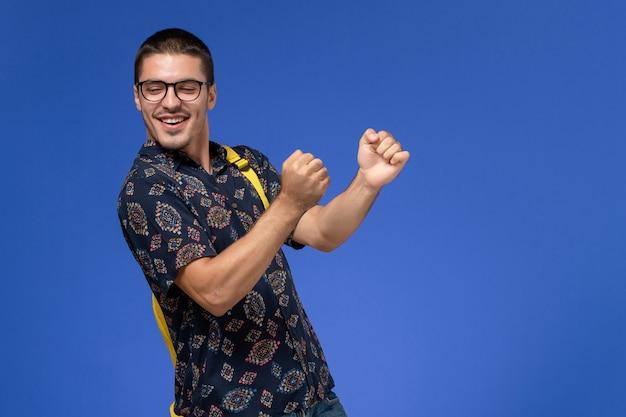 Vorderansicht des männlichen studenten im dunklen hemd, das gelben rucksack tanzt, der auf blauer wand tanzt