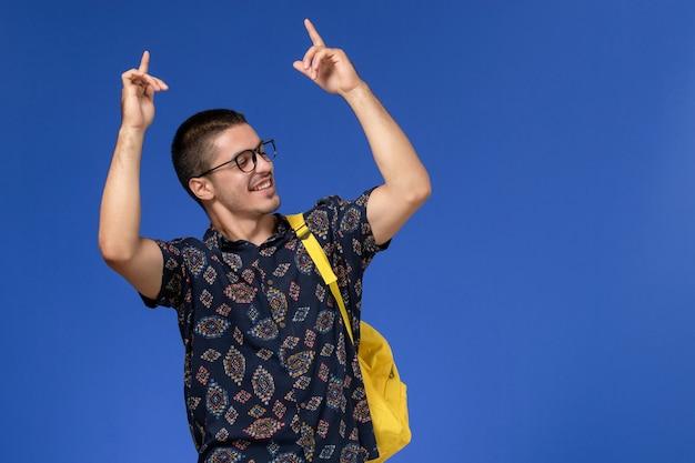 Vorderansicht des männlichen studenten im dunklen hemd, das gelben rucksack trägt, der auf der blauen wand aufwirft und lächelt