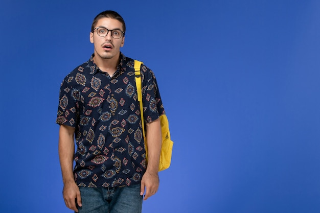 Vorderansicht des männlichen studenten im dunklen hemd, das gelben rucksack trägt, der gerade auf der blauen wand steht