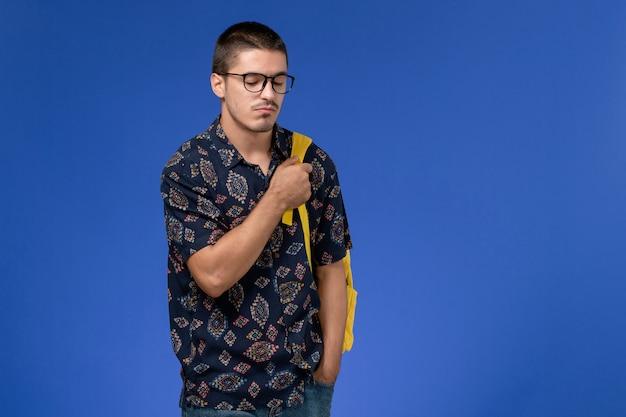 Vorderansicht des männlichen studenten im dunklen hemd, das gelben rucksack trägt, der gerade auf hellblauer wand steht