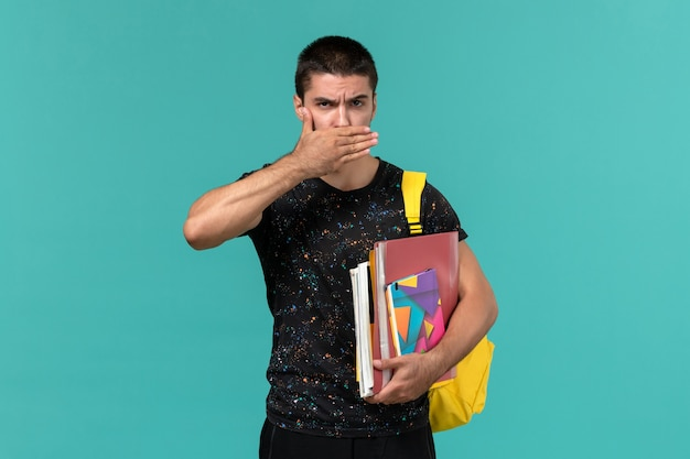 Vorderansicht des männlichen studenten im dunklen t-shirt, das gelben rucksack hält, der heft hält und dateien, die seinen mund auf blauer wand schließen
