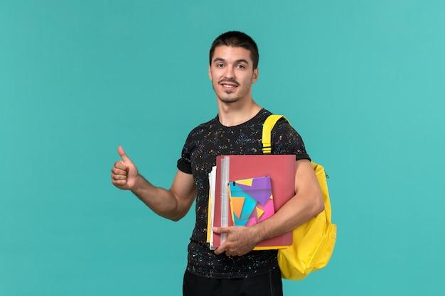 Vorderansicht des männlichen studenten im dunklen t-shirt, das gelben rucksack hält, der heft und dateien auf blauer wand hält