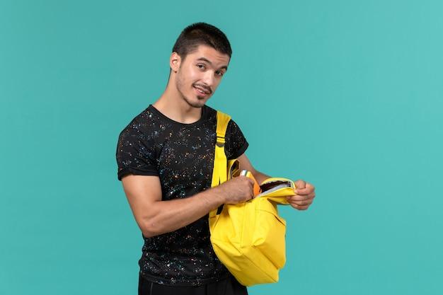 Vorderansicht des männlichen studenten im gelben rucksack des dunklen t-shirts auf hellblauer wand