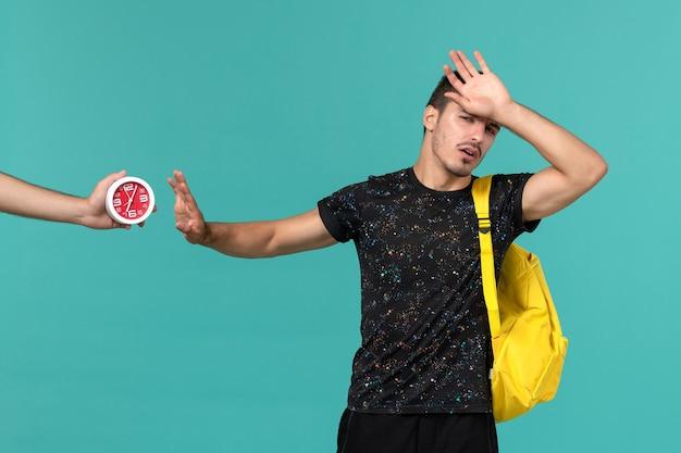 Vorderansicht des männlichen studenten im gelben rucksack des dunklen t-shirts, der auf der hellblauen wand aufwirft
