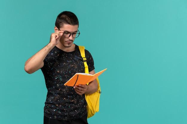 Vorderansicht des männlichen studenten im gelben rucksack des dunklen t-shirts, der das heft auf der blauen wand hält und liest