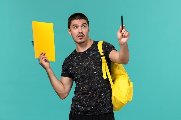 Vorderansicht des männlichen studenten im gelben rucksack des dunklen t-shirts, der dateien und heft auf hellblauer wand hält