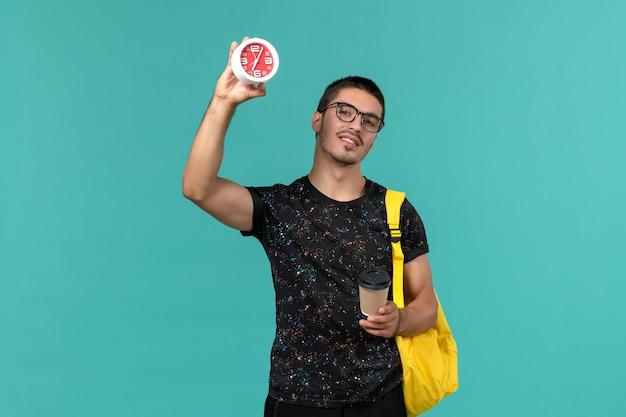 Vorderansicht des männlichen studenten im gelben rucksack des dunklen t-shirts, der kaffee und uhr auf blauer wand hält