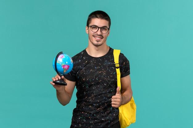 Vorderansicht des männlichen studenten im gelben rucksack des dunklen t-shirts, der kleinen globus auf der blauen wand hält
