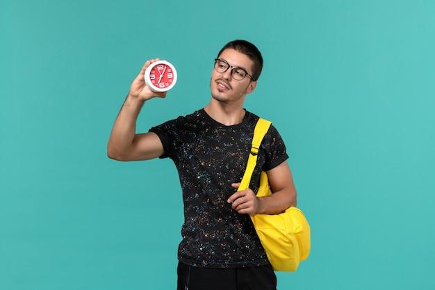 Vorderansicht des männlichen studenten im gelben rucksack des dunklen t-shirts, der uhren an der blauen wand hält