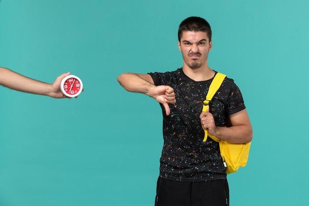 Vorderansicht des männlichen studenten im gelben rucksack des dunklen t-shirts, der unähnliches zeichen auf hellblauer wand zeigt