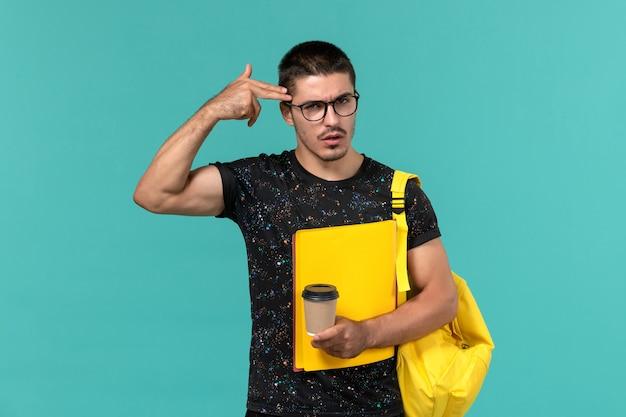 Vorderansicht des männlichen studenten im gelben rucksack des dunklen t-shirts, der verschiedene dateien und kaffee an der blauen wand hält