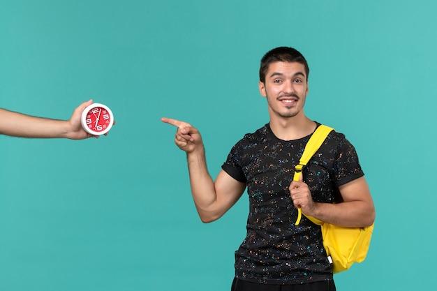 Vorderansicht des männlichen studenten im gelben rucksack des dunklen t-shirts lächelnd auf hellblauer wand