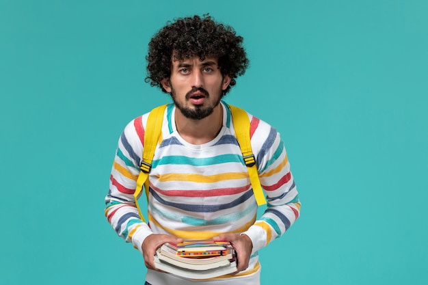 Vorderansicht des männlichen studenten im gestreiften hemd, das gelben rucksack hält, der bücher an der blauen wand hält