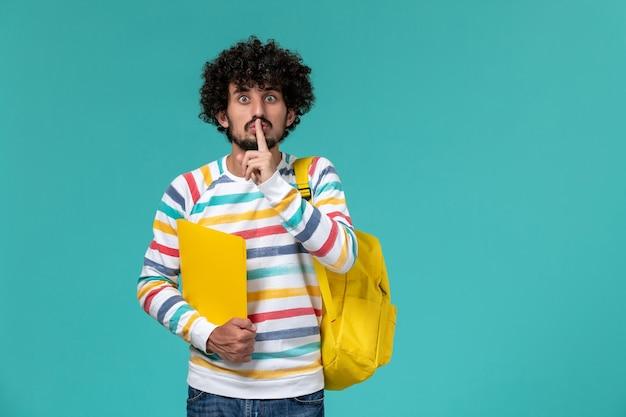 Vorderansicht des männlichen studenten im gestreiften hemd, das gelben rucksack hält, der dateien an der blauen wand hält