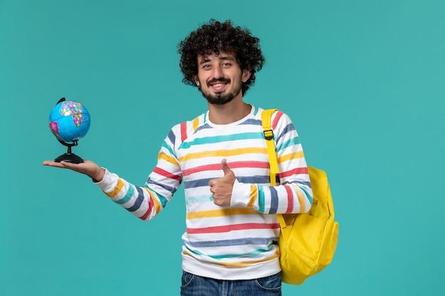 Vorderansicht des männlichen studenten im gestreiften hemd, das gelben rucksack trägt, der runden kleinen globus auf der blauen wand hält