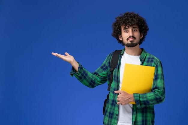 Vorderansicht des männlichen studenten im grünen karierten hemd, das schwarzen rucksack trägt und dateien an der blauen wand hält