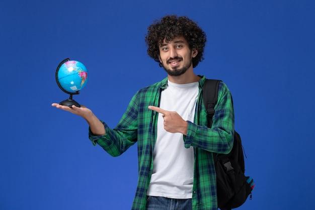 Vorderansicht des männlichen studenten im grünen karierten hemd, das schwarzen rucksack trägt und kleinen globus hält, der auf blauer wand lächelt