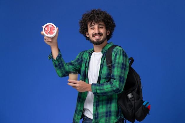 Vorderansicht des männlichen studenten im grünen karierten hemd, das schwarzen rucksack trägt und uhren und kaffee auf blauer wand hält