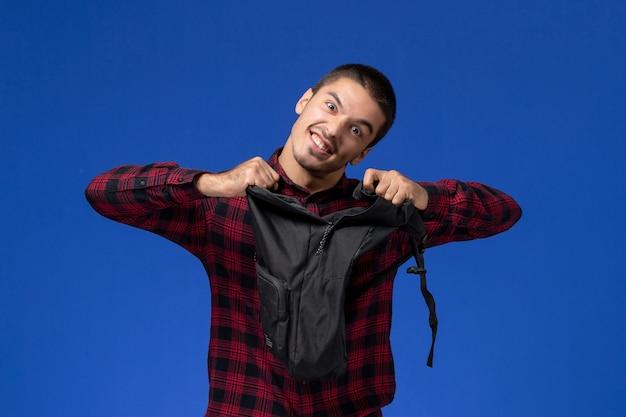 Vorderansicht des männlichen studenten im roten karierten hemd, das seinen rucksack an der blauen wand hält