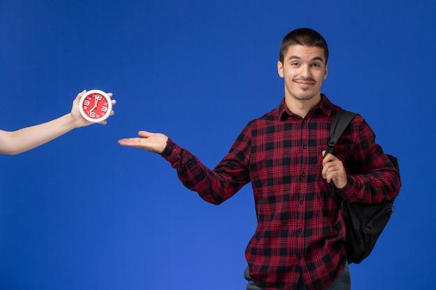 Vorderansicht des männlichen studenten im roten karierten hemd mit dem rucksack, der auf der blauen wand lächelt
