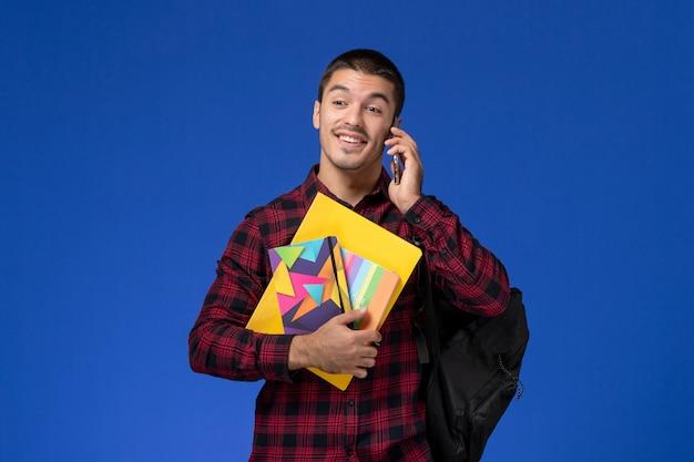 Vorderansicht des männlichen studenten im roten karierten hemd mit dem rucksack, der das heft und die dateien hält, die auf dem telefon an der blauen wand sprechen