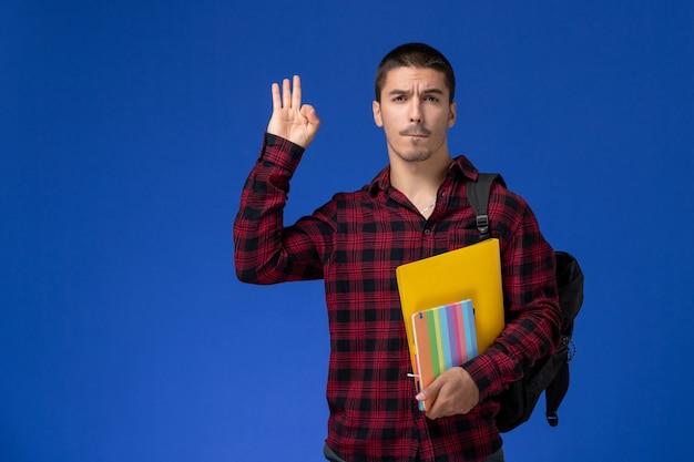 Vorderansicht des männlichen studenten im roten karierten hemd mit rucksack, der dateien und hefte an der blauen wand hält