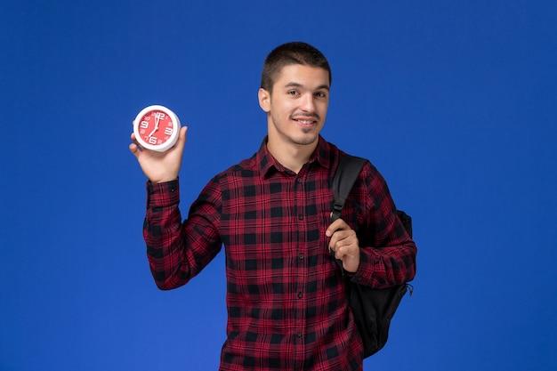 Vorderansicht des männlichen studenten im roten karierten hemd mit rucksack, der uhren an der blauen wand hält