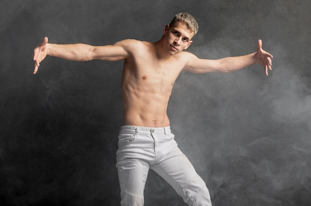 Vorderansicht des männlichen tänzers aufwerfend in den jeans mit rauche