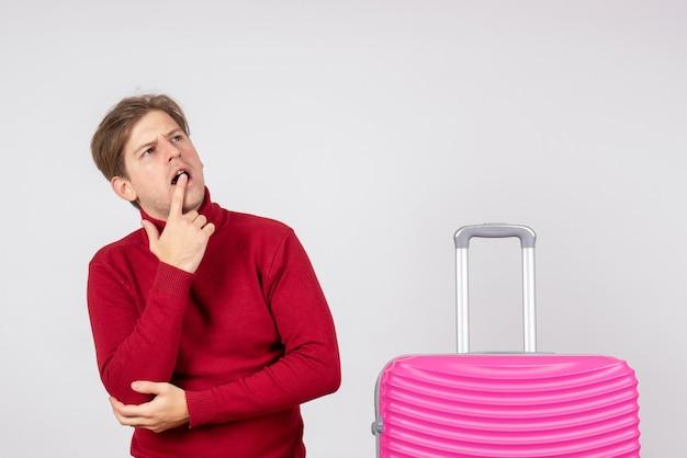 Vorderansicht des männlichen touristen mit rosa tasche auf weißer wand