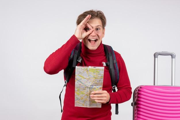 Vorderansicht des männlichen touristen mit rucksack und karte auf weißer wand
