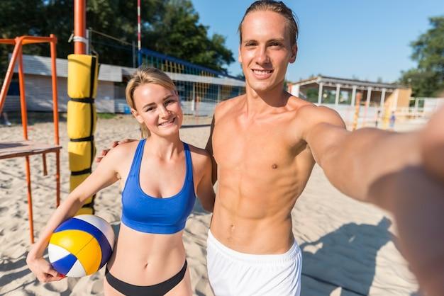 Vorderansicht des männlichen volleyballspielers mit frau, die selfie mit ball nimmt