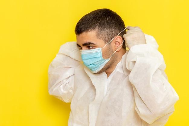 Vorderansicht des männlichen wissenschaftlichen arbeiters im speziellen schutzanzug, der seine maske auf gelbem schreibtisch-wissenschaftsarbeiterkostüm-farbgefahrfoto trägt