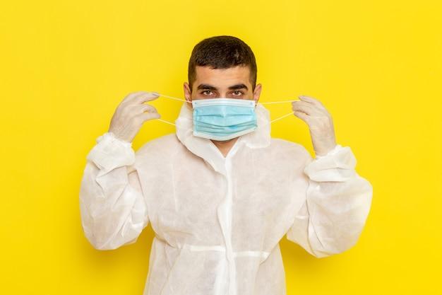 Vorderansicht des männlichen wissenschaftlichen arbeiters im speziellen schutzanzug, der seine maske auf gelber wand trägt