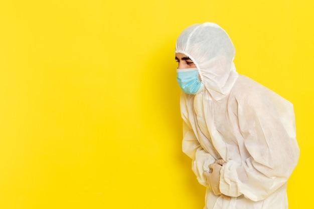Vorderansicht des männlichen wissenschaftlichen arbeiters im speziellen weißen schutzanzug und mit maske, die seinen magen auf hellgelbem schreibtisch-wissenschaftsarbeiterchemie-farbgefahrfoto hält