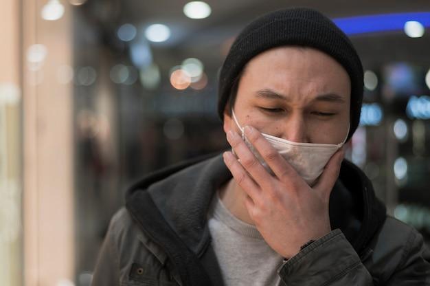 Vorderansicht des mannes am einkaufszentrum, das in der medizinischen maske hustet
